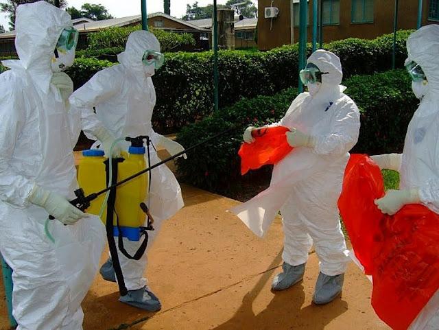 Des employés de l'OMS s'apprêtant à entrer dans l'hôpital de Kagadi dans le district de Kibale où une épidémie d'Ebola a éclaté récemment.