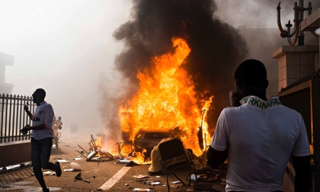 A car burns outside the parliament building in Burkina Faso