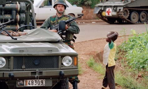 A young Rwanda boy observes a Belgian soldier in defensive position during a halt of a UN convoy in Kigali, April 13, 1994.  The soldiers' mission is to evacuate all foreign citizens from Rwanda to protect them from being massacred by the warring Hutu and Tutsi factions.  (AP Photo/Jean-Marc Bouju)