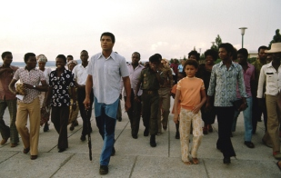 Muhammad Ali walks with fans along the River Zaire before the WBC/ WBA World Heavyweight Title fight against George Foreman at the presidential complex outside of Kinshasa. N'Sele, Zaire 10/1974 (Image # 4031 )