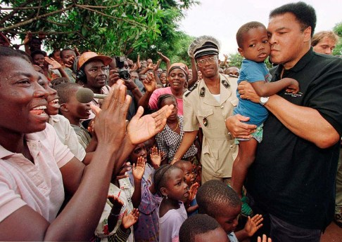 FILE - In this Aug. 20, 1997 file photo, former heavyweight boxing champion Muhammad Ali kisses a Liberian orphan while residents cheer Ali's arrival at an orphanage for Liberian refugees in San Pedro, Ivory Coast. Ali and his entourage came on a goodwill visit to donate food, wheelchairs, and medicine after receiving a letter asking for help from the mission's organizer Sister M. Sponsa Beltran. Ali turns 70 on Jan. 17, 2012. (AP Photo/David Guttenfelder, File)