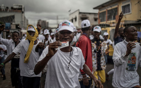 A crowd campaigns under a downpour for a candidate to the Congolese parliament. December 2018, in Kinshasa. Democratic Republic of Congo.